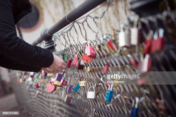 Adult female attaching a love lock to the railings of a metal bridge