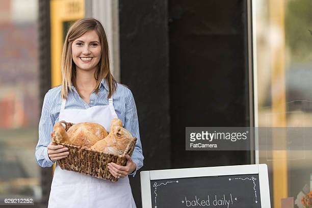 Adult female baker holding basket of bread outside downtown shop
