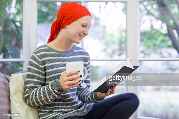 Adult female cancer patient sipping tea and reading a book