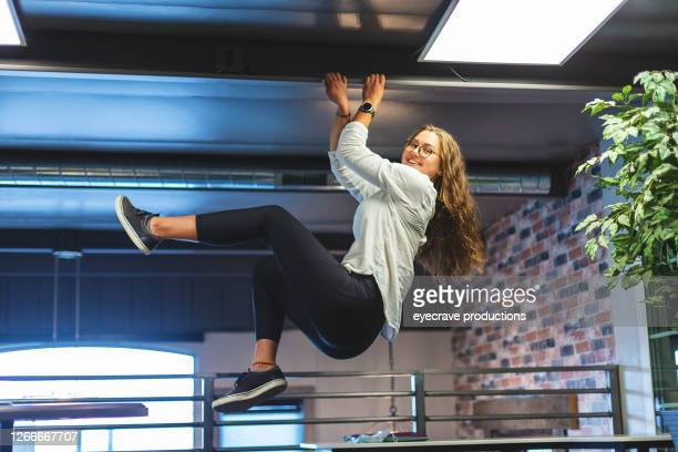 adult female college student hanging from ceiling beam - eyecrave  stock pictures, royalty-free photos & images