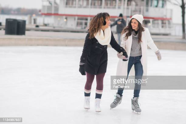 adult female couple ice skating - skating stock pictures, royalty-free photos & images