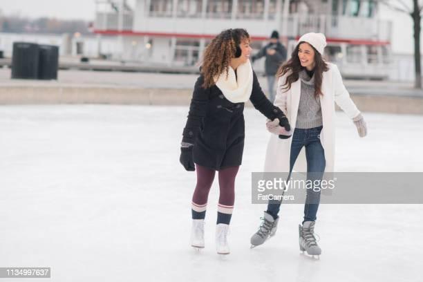 pareja femenina adulto patinaje sobre hielo - patinar fotografías e imágenes de stock