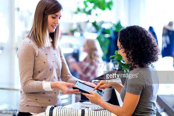 Adult female customer signing a payment with a smart tablet