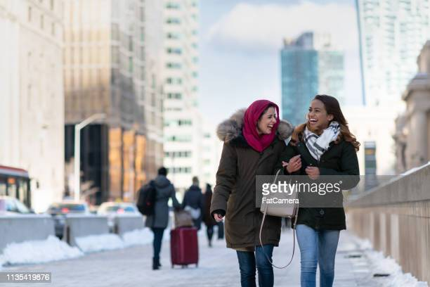 adult female friends walking through the city - emigration and immigration stock pictures, royalty-free photos & images