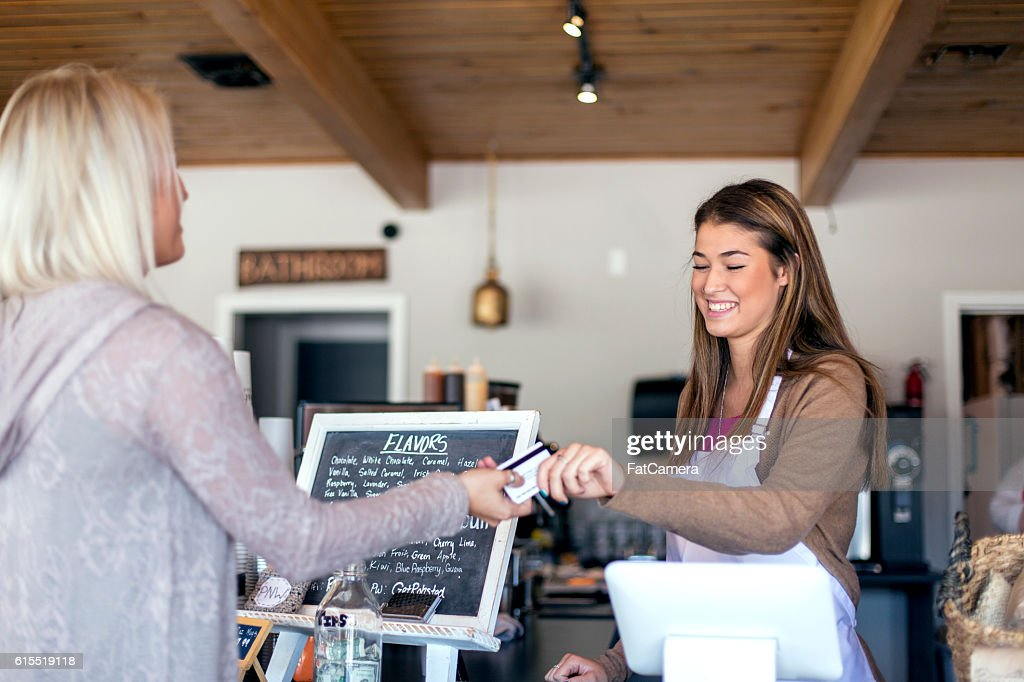 Adult female handing a barista a payment card : Stock Photo