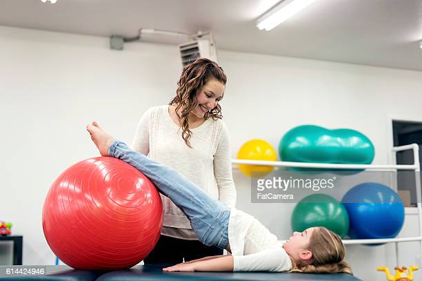 Adult female physical therapist helping a young girl in therapy