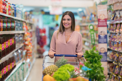 Adult female shopping at the supermarket pushing the cart looking very happy - gettyimageskorea