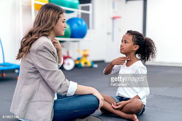 Adult female therapist guiding a young girl in therapy exercises