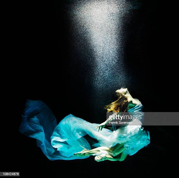 Adult female under water in flowing evening dress