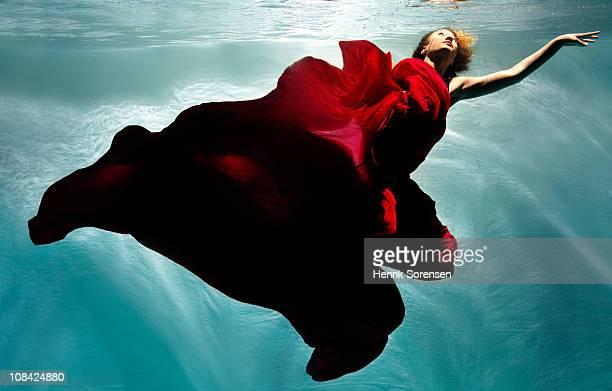 adult female under water in flowing evening dress - vestito rosso foto e immagini stock