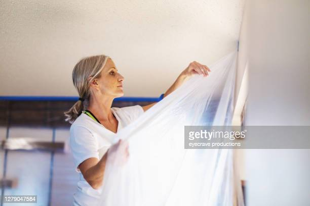 adult female using painter's tape and plastic for painting preparation - eyecrave  stock pictures, royalty-free photos & images