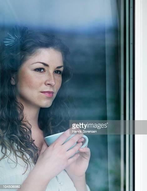 Adult female with a coffee mug by a window