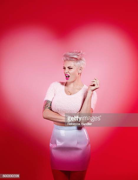 adult female with heart outlined pink backdrop - tattoo designs hearts stock pictures, royalty-free photos & images