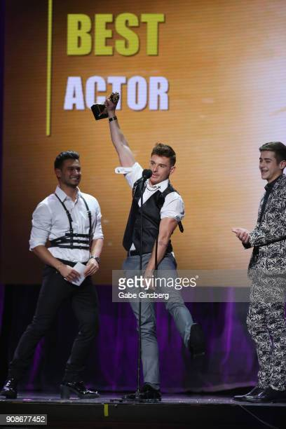 Adult film actor and director Brent Corrigan reacts to winning the Best Actor award while adult film actors Ricky Roman and Joey Mills look on during...