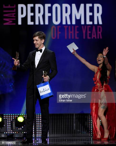 Adult film actor Markus Dupree accepts the award for Male Entertainer of the Year as presenter and adult film actress Gina Valentina cheers during...