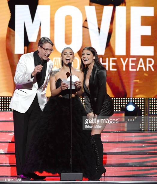 Adult film actor producer and director Steve Holmes and adult film actresses Gina Valentina and Adria Rae present the Movie of the Year award during...