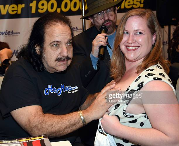 Adult film actor Ron Jeremy poses with Lisa Smith of Utah as adult film actor/director Ed Powers looks on at the HotMoviescom booth at the 2015 AVN...
