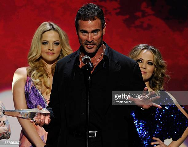 Adult film actor/director Dale DaBone accepts the award for Best Actor as presenters and adult film actresses Alexis Texas and Kristina Rose look on...