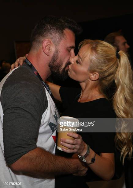 Adult film actor/director Manuel Ferrara kisses adult film director/actress Kayden Kross at the Rock Candy/bedroom Products booth during the 2020 AVN...
