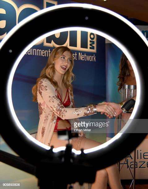 Adult film actress Alexa Grace shown through a ring light greets attendees at the Adult Entertainment Broadcast Network booth at the 2018 AVN Adult...