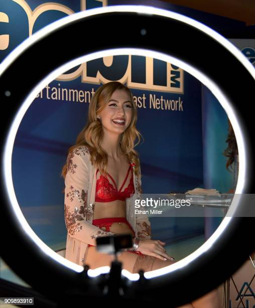 Adult film actress Alexa Grace shown through a ring light smiles at the Adult Entertainment Broadcast Network booth at the 2018 AVN Adult...