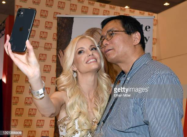 Adult film actress Charlotte Stokely takes a selfie with Ken Chow at the AVN Stars booth at the 2020 AVN Adult Entertainment Expo at the Hard Rock...