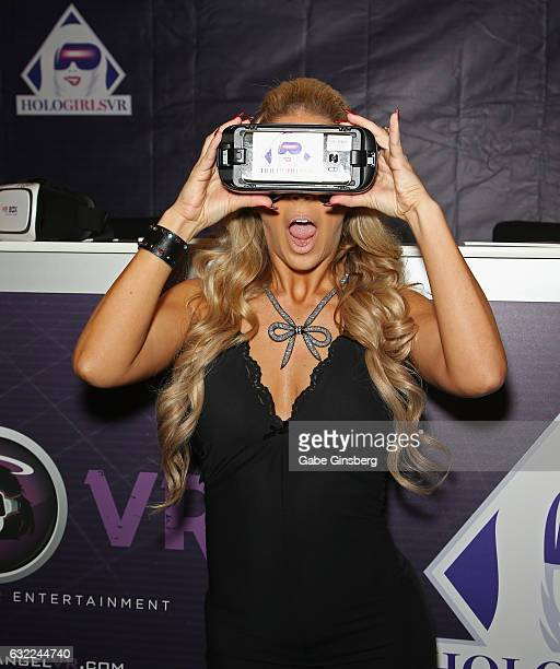 Adult film actress Cherie DeVille demonstrates how to watch HoloGirls VR movies on a virtual reality headset at the HoloGirls VR booth during the...
