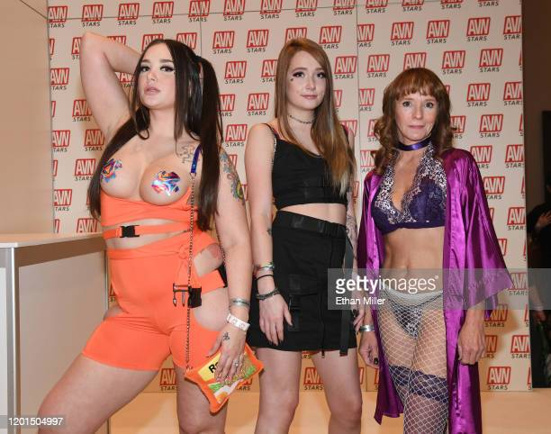 Adult film actress Gia Paige her sister webcam model The Baby Paige and adult film actress Cyndi Sinclair pose at the AVN Stars booth at the 2020 AVN...