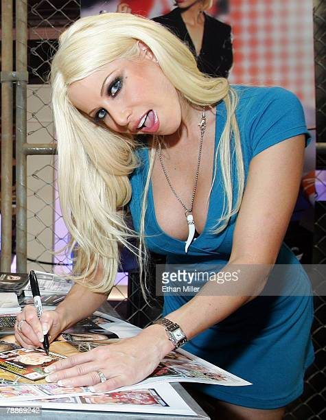 Adult film actress Gina Lynn looks up while signing autographs for attendees at the Jules Jordan video booth at the 2008 AVN Adult Entertainment Expo...