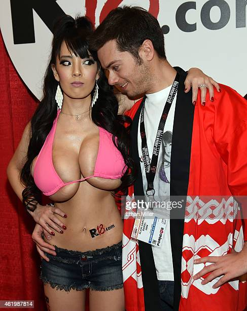 Adult film actress Hitomi Tanaka and Alain Garcia Bariel joke around at the R18.com booth at the 2015 AVN Adult Entertainment Expo at the Hard Rock...