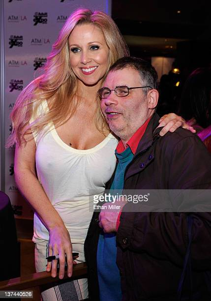 Adult film actress Julia Ann takes a photo with attendee Tony Hunt of England at the 2012 AVN Adult Entertainment Expo at The Joint inside the Hard...