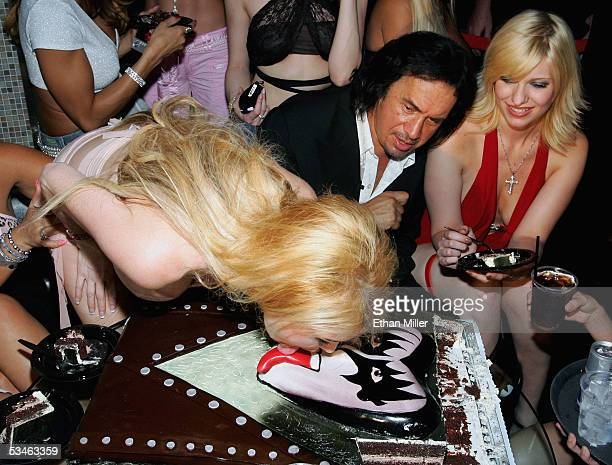 Adult film actress Taylor Wane licks the tongue on Kiss singer/bassist Gene Simmons' birthday cake as he looks on during his birthday party at the...