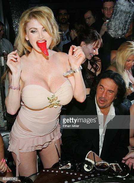 Adult film actress Taylor Wane plays with the tongue from Kiss singer/bassist Gene Simmons' birthday cake as he looks on during his birthday party at...