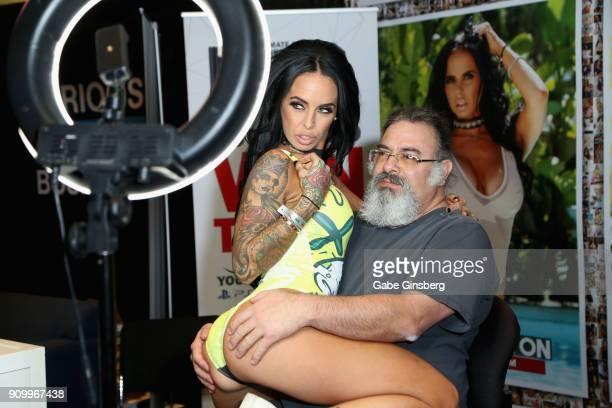 Adult film actress/director Brandy Aniston poses with an attendee in her booth during the 2018 AVN Adult Entertainment Expo at The Joint inside the...