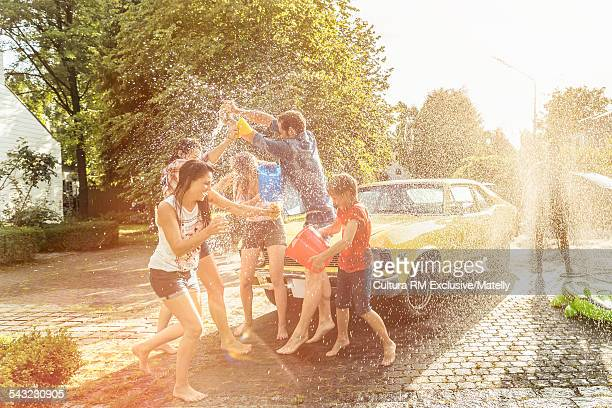 Adult friends and boy having water fight whilst washing vintage car