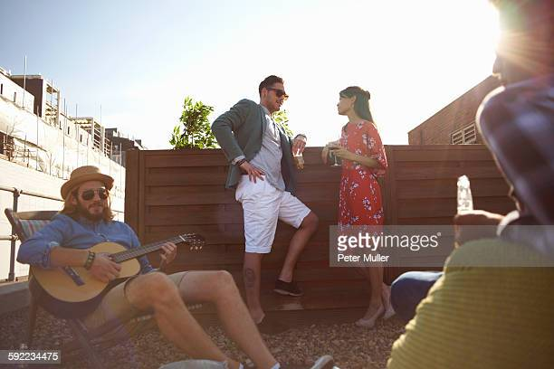 Adult friends chatting and playing guitar at rooftop party
