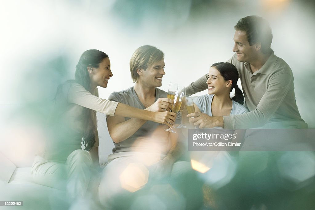 Adult friends clinking champagne glasses, smiling : Stock Photo