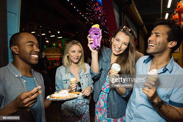 Adult friends eating ice creams in amusement park at night, Santa Monica, California, USA