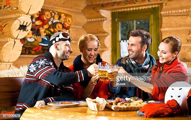 Adult friends having lunch, toasting with beer