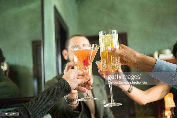 adult friends holding up cocktails raising a toast in recreational bar - heshphoto stock pictures, royalty-free photos & images