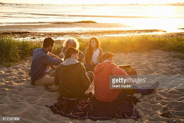 Adult friends picnicing at sunset on Bournemouth beach, Dorset, UK