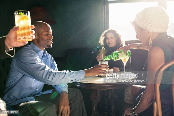 adult friends pouring beer at table whilst socialising in recreational bar - heshphoto photos et images de collection