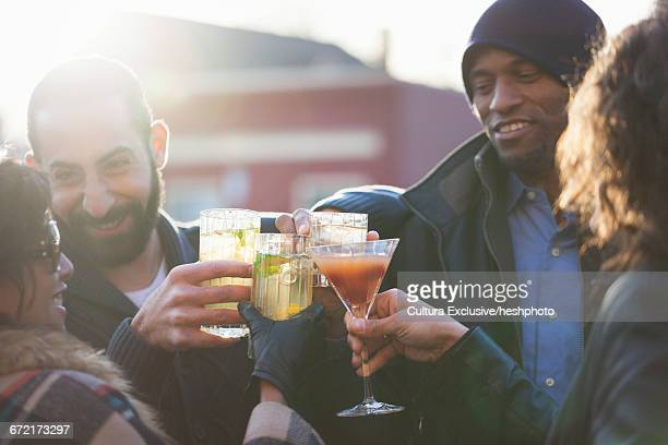 adult friends raising a cocktail toast at recreational bar patio - heshphoto stock pictures, royalty-free photos & images