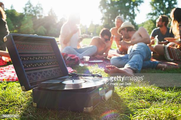 Adult friends relaxing and listening to record deck at sunset park party