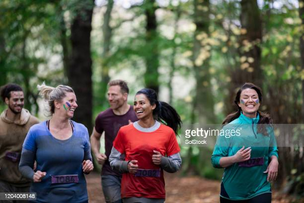 adult friends running outdoors in country park - 30 39 years stock pictures, royalty-free photos & images