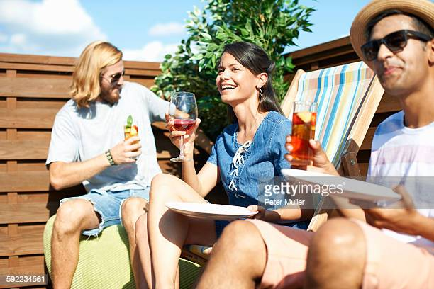 Adult friends sitting on deck chairs drinking at rooftop party