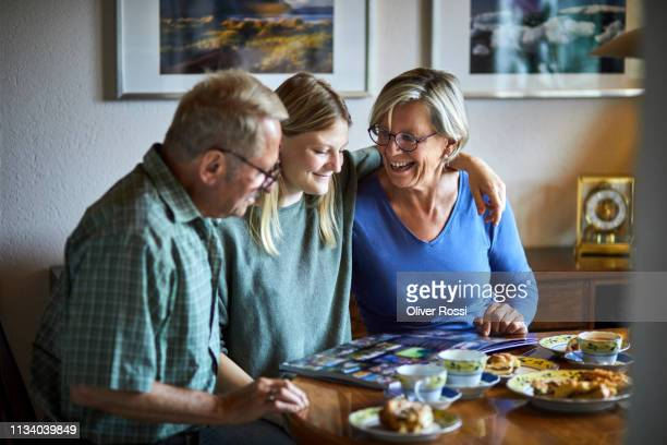 adult granddaughter and grandparents sitting at dining table looking at photo album - album photo femme photos et images de collection