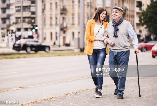 adult granddaughter assisting her grandfather strolling with walking stick - doing a favor stock pictures, royalty-free photos & images