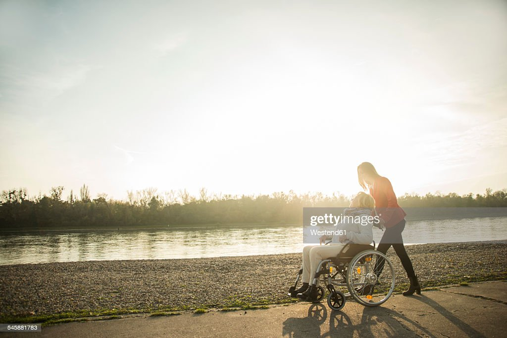 Adult granddaughter assisting her grandmother sitting in wheelchair : Stock Photo