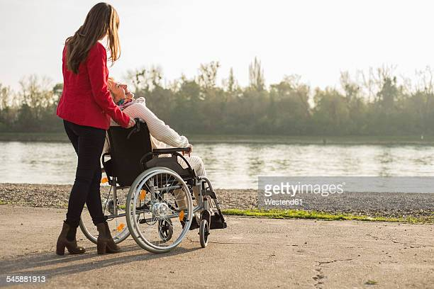 Adult granddaughter assisting her grandmother sitting in wheelchair